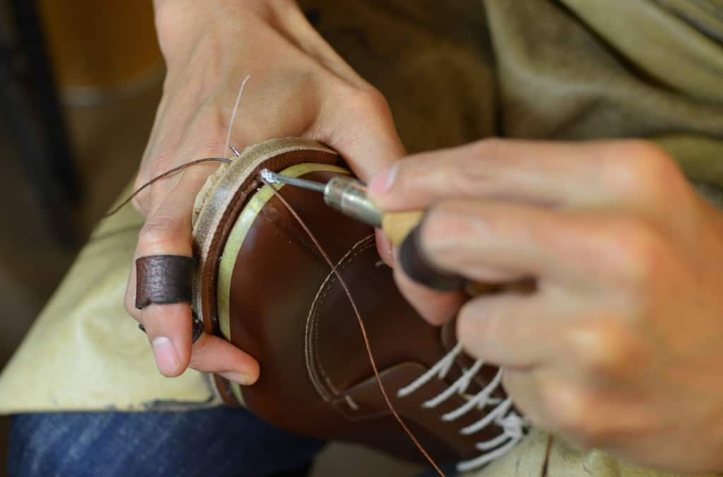 Sole stitch is made. You can see how they have rolled a fudge wheel on top of the welt with the desired distance between the dimples, in which each stitch will be placed.