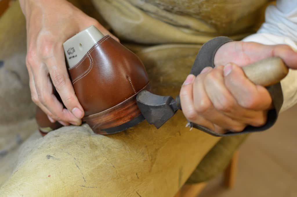 The sole and heel edge has been colored and polished, and now a hot iron burn in the color in the leather.