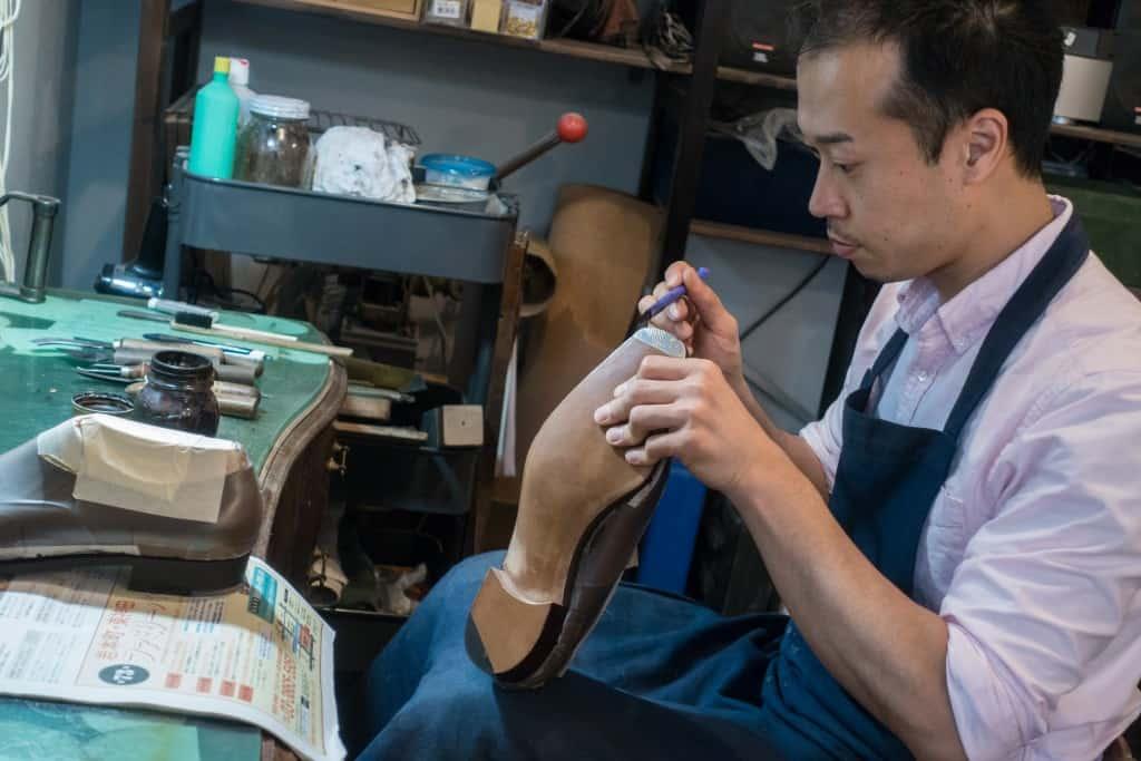 The apprentice Akira Igarashi doing some sole edge finishing.
